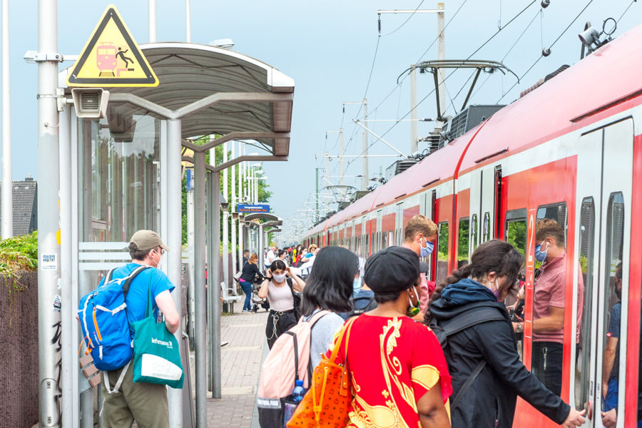 Resiende drängen sich auf dem schmalen Bahnsteig in Kerpen Sindorf